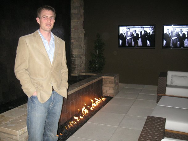 Tyler Jones, the president of Blue Heron development, stands in the courtyard (complete with waterfall, fire and flatscreens) he helped design and build.