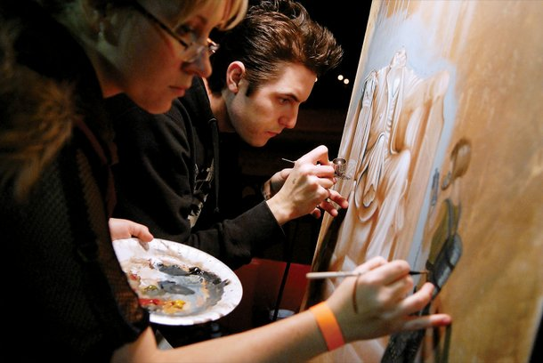 Mike and Dasha Biggs paint on canvas inside the Canvas Cafe.