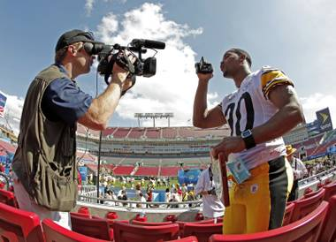 Pittsburgh Steelers' Roy Lewis films a cameraman while being interviewed during the team's media day for Super Bowl XLIII Tuesday, Jan. 27, 2009, in Tampa, Fla.