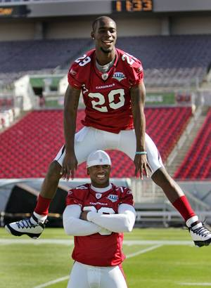Arizona Cardinals' Dominique Rodgers-Cromartie leaps over teammate Ralph Brown during Super Bowl XLIII media day at Raymond James Stadium Tuesday Jan. 27, 2009, in Tampa Bay, Fla.