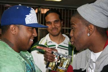 Local rap artists King Lo, left, and Artisan freestyle rap battle while host Omar Starr from Power 88 watches in the background.