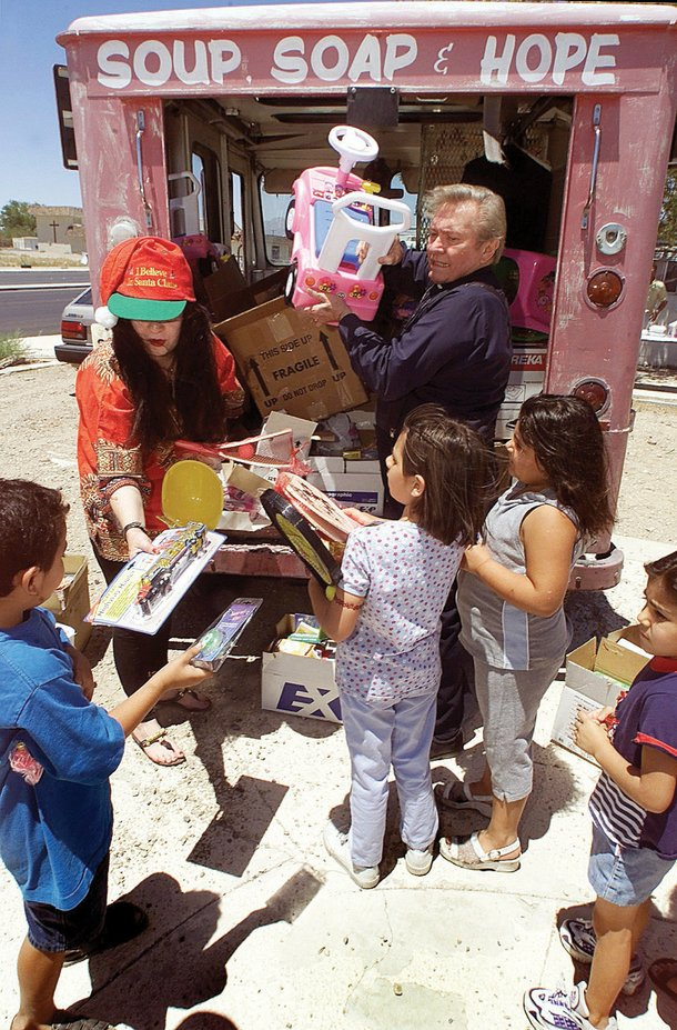 Magickal Marissa and John 3:16 Cook distribute toys to children (2000).