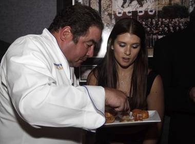 Emeril Lagasse and Danica Patrick dig into some snacks at the grand opening of Lagasse's Stadium on September 24, 2009.