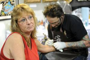 A woman gets ink at the Biggest Tattoo Show on Earth.