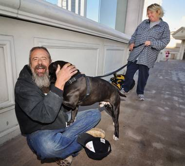 Andy Smith is greeted by Tawnee Roberts and her dog, Concord, on the pedestrian bridge where homeless man 