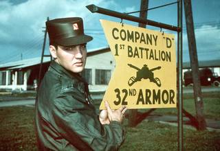 The undated file photo shows Elvis Presley beside a sign of his US Army unit in Friedberg, Germany, where he spent 18 months between 1958 and 1960. (AP Photo)