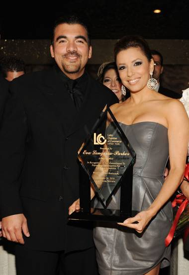 "Eva Longoria Parker recieves the ""Premio de Oro"" award from Latin Chamber of Commerce Chairman Luis Valera on Saturday, February 20, 2010."