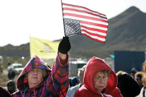An attendee displays her sentiments by waving a U.S. flag upside down.