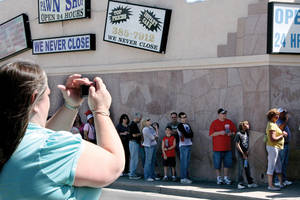 Visitors cross Las Vegas Blvd. to take pictures of friends and family waiting in line at Gold & Silver Pawn.