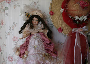 One of the many porcelain dolls lining the walls at Olivia's Dollhouse Tea Room.