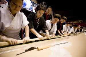 Student sushi cooks help assemble a 40-foot sushi roll at Taste of UMass.