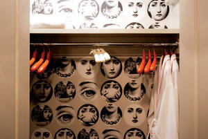Look closely: Fornasetti wallpaper in a guestroom closet.
