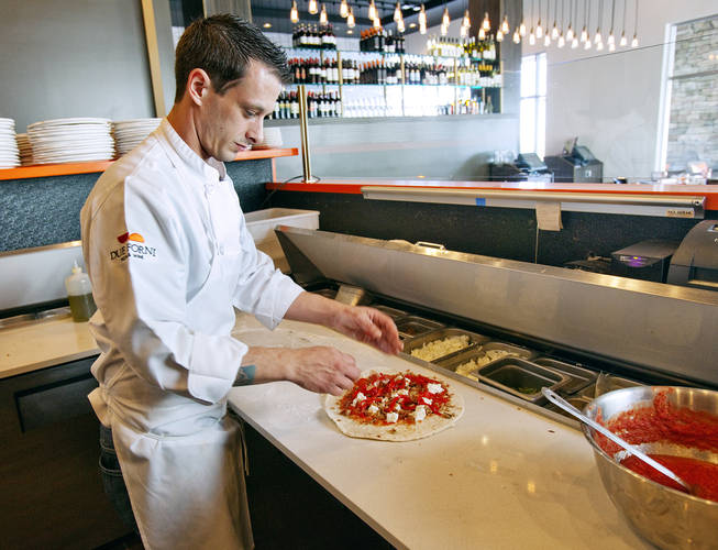A cook prepares one of the seven pizzas offered at Due Forni.