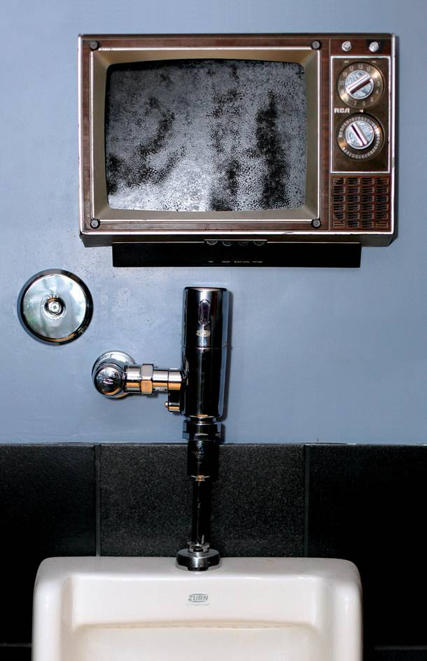 Old television sets were turned into frames for artwork in the men's room at Artifice.
