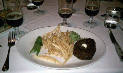 A flat iron steak with housemade french fries, foie gras buttered haricot vert sachet and maitre d' butter