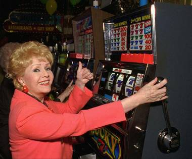 Entertainer Debbie Reynolds pulls the handle of a slot machine inside the Debbie Reynolds Hotel & Casino in Las Vegas on Oct. 1, 1997. Reynolds would file bankruptcy later that year and sell the property for $10 million to the company behind the World Wrestling Federation.