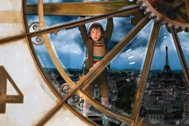 Hugo (Asa Butterfield) hangs around a Paris train station.