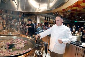Jaleo chef Jose Andres works on browning chicken and rabbit in one of his massive paella pans during Vegas Uncork'd on May 11, 2012.