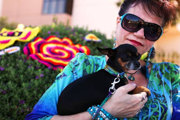 Shannon Paul sits with her dog Miss Mouse, who is sporting a crocheted collar and leash, near the yarn-based public art project installed on the pedestrian bridge across Maryland Parkway north of Desert Inn Road in Las Vegas on Monday, June 11, 2012.