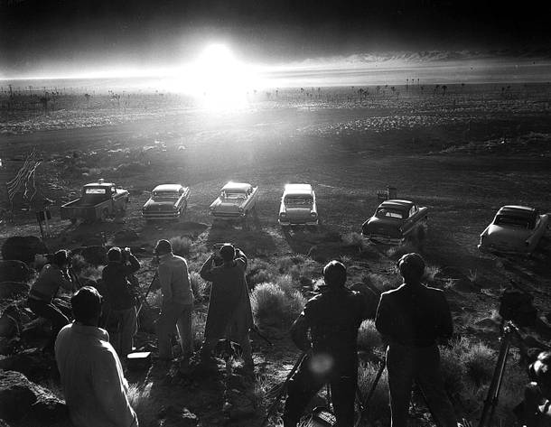 In this June 24,1957 photo from the Las Vegas News Bureau, photographers are seen lined up to shoot the above ground detonation of a bomb at the Nevada test site.