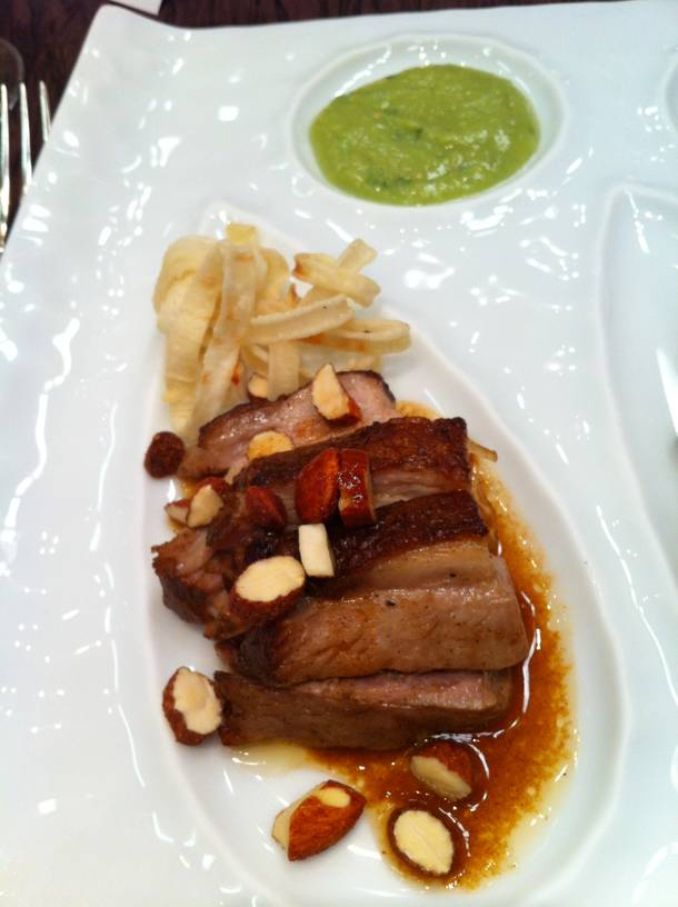 Chef Edmund Wong's braised pork belly with smoked almonds, fried onions and an avocado-jalapeño salsa verde.