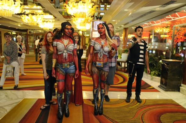 Marvick (in the background) walks with his fellow Naked Vegas employees and two of their body painting masterpiece models. The local body painting company is now being featured on Syfy's new reality program, Naked Vegas.