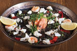 Toros' <em>paella negra</em> is black rice laced with shrimp, squid and crab meat.
