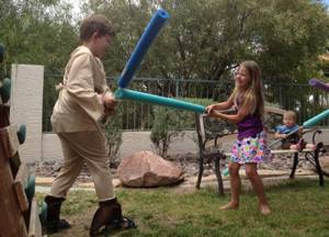 Christopher Belew and Erin Harris demonstrate their foam-noodle lightsaber skills while Jedi-in-training Tegan DeWald looks on.