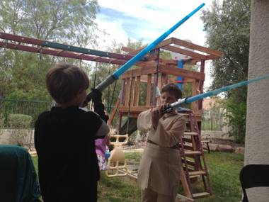 Darth Vader (Zander Toussaint) and Obi-Wan (Christopher Belew) battle it out. It was a great way to limber up for the Death Star piñata at the Jedi Scouts' Star Wars Day bash.