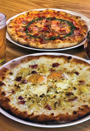 Flour & Barley's Calabrese pie (top) has meatball, sausage, prosciutto cotto, mozzarella, Calabrian chili and salsa verde; the Carbonara boasts mozzarella, pancetta, roasted cauliflower, black pepper, and fresh farm eggs.