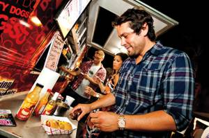Augie, 31, adds some sauce to his specialty hotdog from the Sin City Dog truck at the August 2013 installment of the Vegas StrEATs festival.