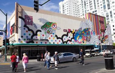 Pedestrians pass by a mural by Sush Machida and Tim Bavington on the Emergency Arts building in downtown Las Vegas Tuesday, Oct. 21, 2014.