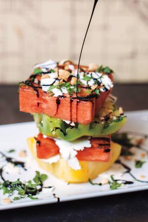 Go easy at Public School 702 with the grilled watermelon and tomato stack.