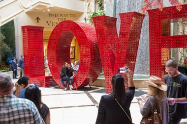 Shoppers take photos with the new 'LOVE' sculpture at Palazzo's Grand Canal Shoppes.
