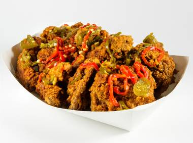 All mixed up with vinegary hot sauce and pickled peppers are crispy chicken necks, backs, hearts and gizzards.