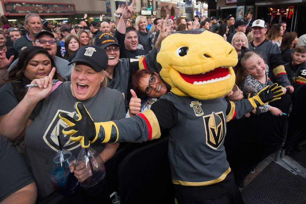 282f50a27969 Vegas Golden Knights mascot Chance the Golden Gila Monster poses with fans  during a Vegas Golden Knights Fan Fest at the Fremont Street Experience.