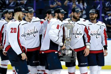 Team members of the Washington Capitals hold the NHL Eastern Conference championship trophy