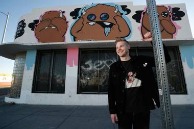 Ryan Brunty poses in front of his mural at Fremont and 11th streets.