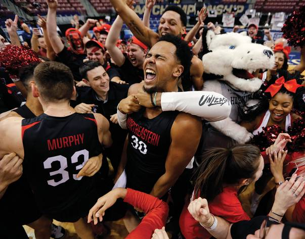 Northeastern's Anthony Green celebrates with temmates and fans after the Huskies defeated Hofstra 82-74 to win the Colonial Athletic Association men's basketball championship March 12. <em>(Mic Smith / AP)</em>