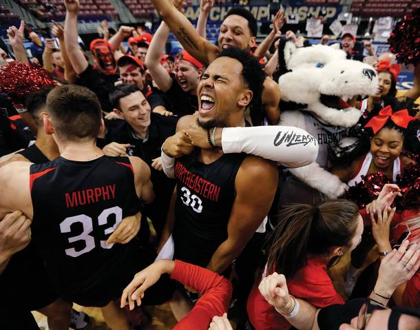 Northeastern's Anthony Green celebrates with temmates and fans after the Huskies defeated Hofstra 82-74 to win the Colonial Athletic Association men's basketball championship March 12. (Mic Smith / AP)